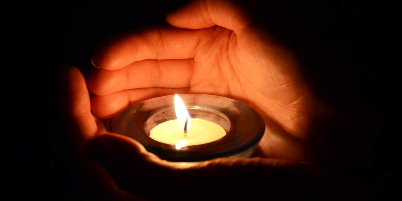 cupped hands around candle flame